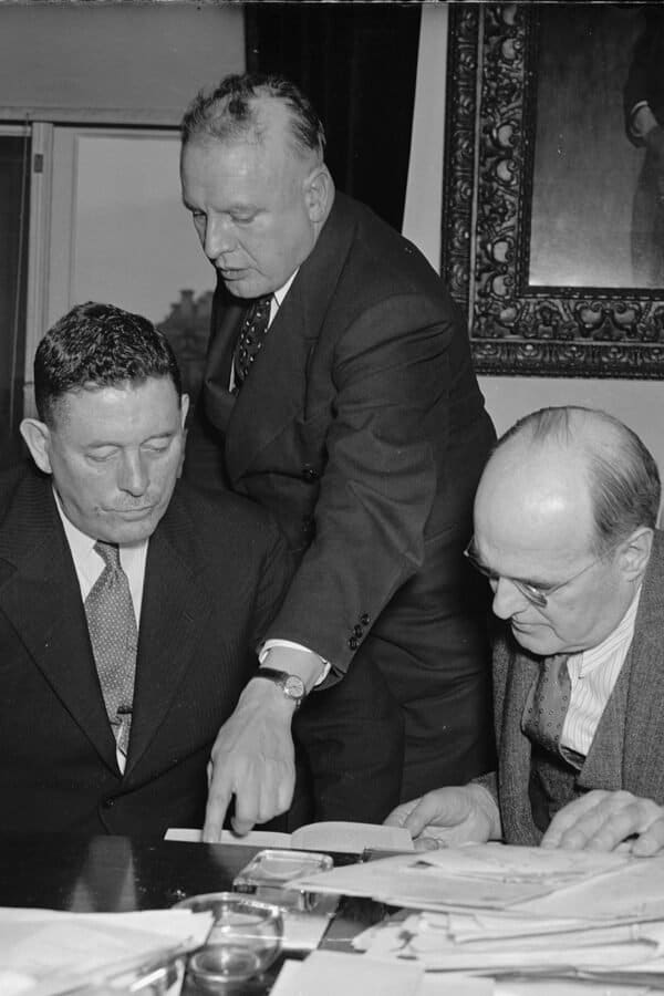 In the photograph, left to right: Col. C.H.L. Sharman, Chief of Canadian Narcotic Control; Harry Anslinger, U.S. Commissioner of Narcotics; and Assistant Secretary of Treasury Stephen B. Gibbons