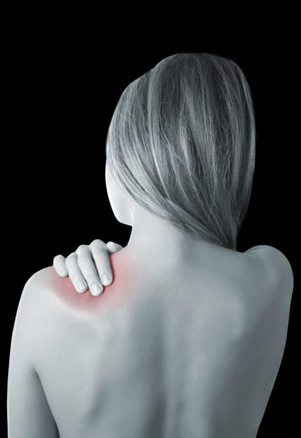 Rückenansicht einer jungen Frau mit Schulterschmerzen.