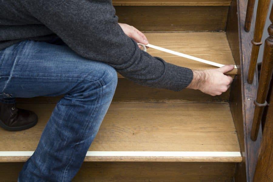 Mann klebt reflektierendes Klebeband auf die Stufe einer Holztreppe