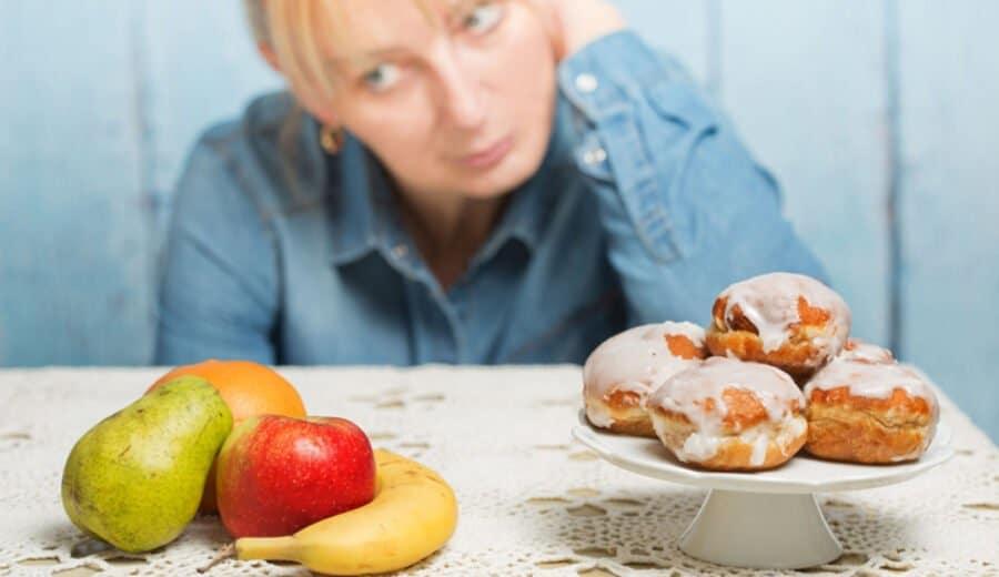 Frau  wählt zwischen Obst und Süssigkeiten