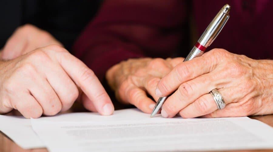 Hände einer älteren Dame, die auf ein Blatt Papier schreibt