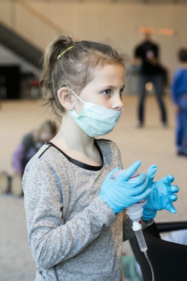 """Mädchen spielt """"Dökterle"""" und trägt Handschuhe sowie einen Mundschutz"""